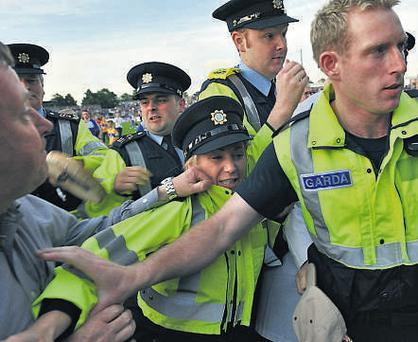 Gardai are forced to escort the umpire off the pitch as furious Clare supporters vent their anger after last night's Munster U21 hurling final