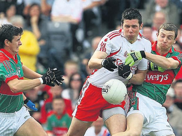 Sean Cavanagh tries to escape the attentions of Aidan Higgins and Keith Higgins.