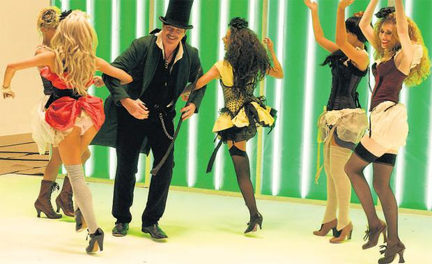 Actor Patrick Bergin cavorts with scantily clad dancers in the video