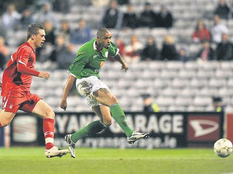 Ireland's Caleb Folan scores his side's first goal despite the attempts of Luke Chambers at Dalymount Park last night