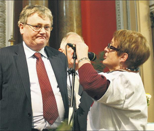Junior health minister, John Moloney, being heckled by pensioner Margaret Gaynor as 1,400 pensioners gathered at Westland Row Church, Dublin