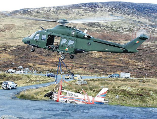 The fuselage of the Piper PA-28 light aircraft that crashed on Church Mountain, Co Wicklow, killing the four occupants is lifted from the site by an Army Air Corps helicopter
