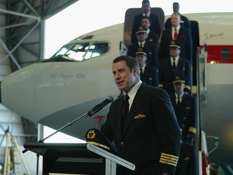 John Travolta speaks at a function celebrating the 50th anniversary of Qantas trans-Pacific services to the USA at Hangar One, Brisbane International Airport May 12, 2004 in Brisbane, Australia <b>Photo:</b> Getty Images