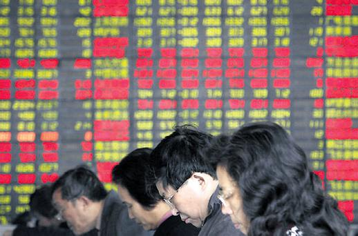 Investors check and trade stocks at a securities trading firm in Shanghai, China, yesterday. Asian stocks fell, led by banks and commodity companies, on scepticism that the proposed US bank rescue will revive credit markets and the world's biggest economy