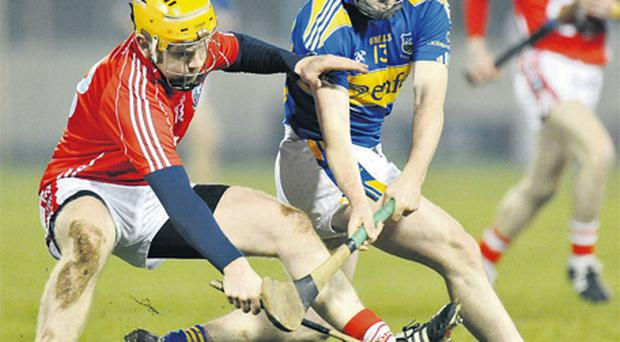 Cork's Joe Moran and Pat Kerwick of Tipperary tussle for the ball during last night's NHL Division 1 clash in Semple Stadium