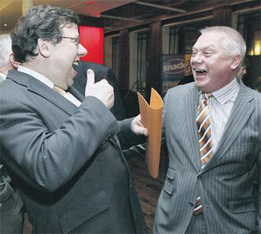 Taoiseach Brian Cowen shares a laugh with Paidi O Se at a special 20th anniversary of the player's football tournament after he had endured a tough day in the Dail where he was grilled by the Opposition on the banking crisis