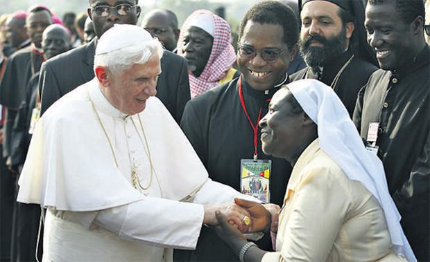 Pope Benedict XVI is welcomed by a nun on his arrival at the airport in Yaounde, the capital of Cameroon