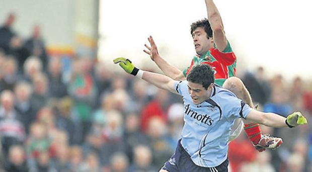 Patrick Harte of Mayo leaps alongside Dublin's Ross McConnell during their game in Ballina