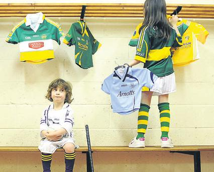 Peter Catterson (4) from Dublin waits on Charlotte Cantwell (7) as she hangs up county jerseys at the launch of TV3's GAA schedule