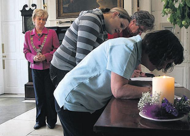 SHOWING SOLIDARITY: Lord Mayor of Dublin, Eibhlin Byrne, looks on as people sign a Book of Solidarity for those who suffered abuse, in The Mansion House, yesterday. Photo: Tony Gavin