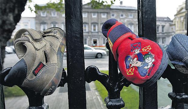 Children's shoes left on the railings of Dail Eireann yesterday ahead of today's protest by victims of abuse