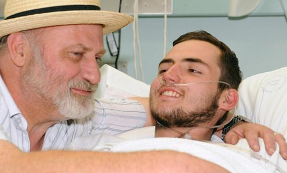 British backpacker Jamie Neale, right, is embraced by his father Richard at a hospital in Katoomba, west of Sydney