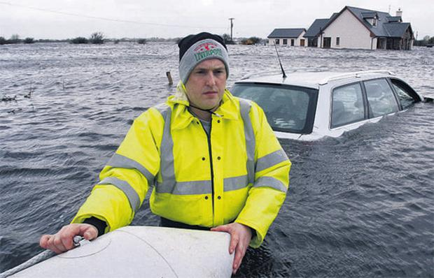Liam Kehoe waist deep in water with his new house flooded in the backround at Caherlea, near Claregalway, Co Galway, yesterday