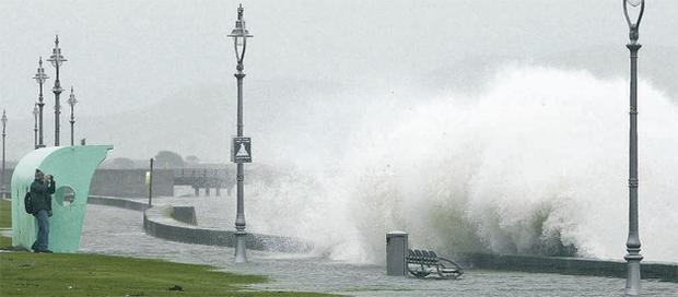 A passer-by takes a photograph as a giant wave crashes over the sea wall at Clontarf in Dublin yesterday