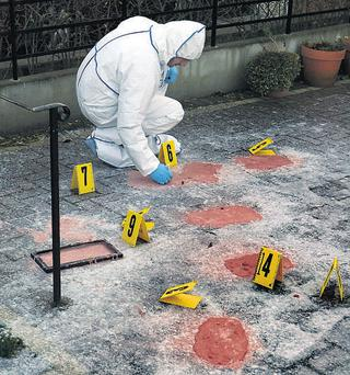 A garda forensic officer takes shoe print plaster casts at the scene of the tiger kidnapping in Dublin