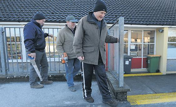 The principal of Listellick National School in Co Kerry, Micheal O Cinneide (right), with work men James and Pat Fitzgerald, hold tightly on to the railing as they move about the ice-covered school yard yesterday