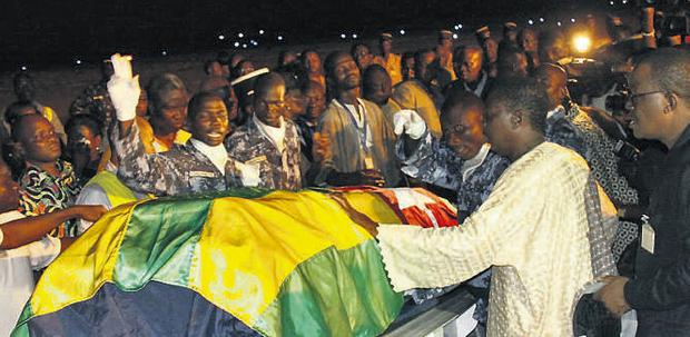 Togolese government officials and relatives receive the remains of Togolese assistant soccer coach Amalete Abalo in the country's capital of Lome on Sunday