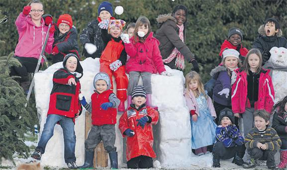 Children playing in the snow near a newly built snow igloo at Bridgefield, Killarney, Co Kerry, yesterday