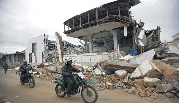 Police officers pass a destroyed building in the town of Constitucion, Chile, yesterday