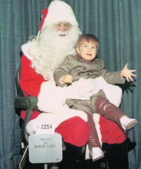 Upset boy sitting on lap of Santa Claus