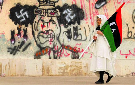 A Libyan woman holding a Kingdom of Libya flag walks past a caricature of Muammar Gaddafi in Benghazi in this June 8, 2011 file photo. In post-revolution Libya, Egypt and Tunisia, women are exploring what the Arab Spring means for them. Since long-time leaders were toppled in the three north African states, many -- not least in the West -- fret the power vacuum will leave the door open for Islamist groups to take power and force changes that will damage women's rights. To match feature ARABS-WOMEN/ REUTERS/Esam Al-Fetori/Files (LIBYA - Tags: POLITICS CIVIL UNREST)