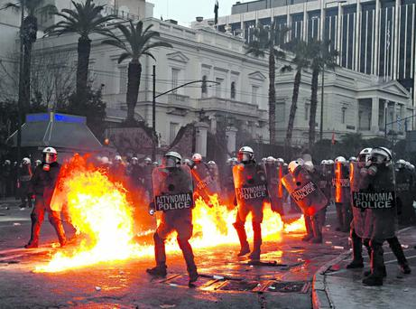 A petrol bomb explodes near riot police during a huge anti-austerity demonstration in Athens' Syntagma (Constitution) square February 12, 2012. Greek lawmakers looked set to endorse a new and deeply unpopular austerity deal on Sunday to secure a multi-billion-euro bailout and avert what Prime Minister Lucas Papademos warned would be
