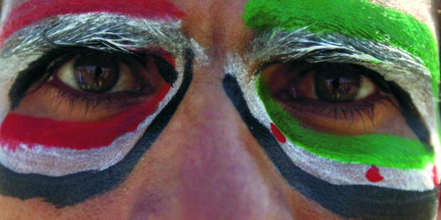An anti-government protester paints the colours of the national flags of Yemen and Syria around his eyes during a march in solidarity with the people of Syria in Sanaa February 12, 2012. REUTERS/Mohamed al-Sayaghi (YEMEN - Tags: POLITICS CIVIL UNREST)