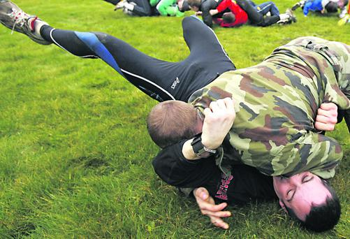 Ireland's Darren O'Neill wrestles with a Defence Forces Instructor during the Irish Defence Forces endurance and team building assault course at the Curragh Army Camp, Curragh. PRESS ASSOCIATION Photo. Picture date: Friday February 17, 2012. Photo credit should read: Julien Behal/PA Wire.
