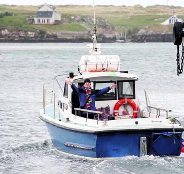 Barry Edgar Pilcher waves as he returns to Inishfree Island following his weekly shop in Burtonport, Co. Donegal. Pic: Declan Doherty