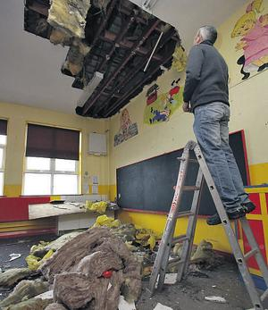 Caretaker Francis McGowan inspecting the damage done by burst pipes in one of the classrooms at Our Lady of Mercy Primary School, Sligo, yesterday