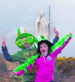 Molly and Cian Navin were all geared up for the big day as they visited Croagh Patrick, Mayo's holy mountain, watched over by a statue of the mighty man himself. Photo: PAUL MEALEY