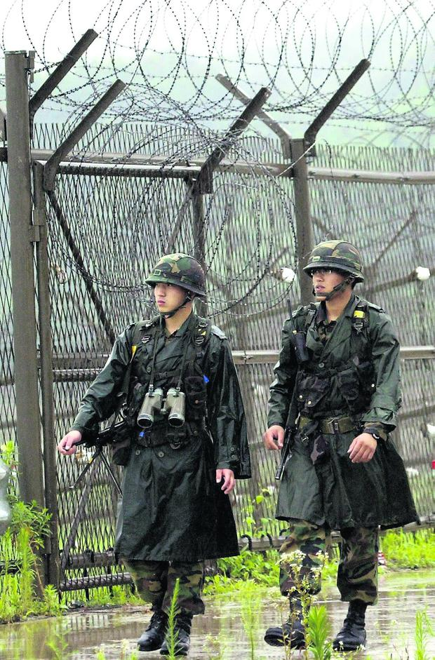South Korean soldiers patrol along a barbed-wire fence in Imjinkak, near the demilitarized zone which separates the two Koreas in Paju, about 50 km (