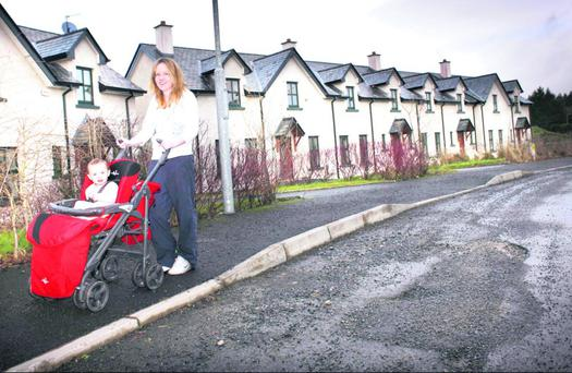Aisling Murray pushes her daughter Katie past a row of empty houses in a Drumshanbo 'ghost estate' in Co Leitrim