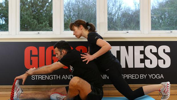 Yoga guru Sarah Ramsden supervises Ryan Giggs as he does some stretches during the launch of his Giggs Fitness DVD in Manchester. Photo: Getty Images