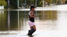 A woman walks through floodwaters. The devastating floods have affected some 200,000 people and have forced many homes to be evacuated