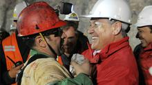 Chile's President Sebastian Pinera (right) hugs rescued miner Mario Sepulveda, the second man to be lifted to safety