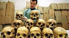 Bosnian pathologist Rifat Kesetovic as he examines skulls of victims in a hospital in Tuzla, March 28, 1997, taken from mass graves and in wooded areas following the 1995 massacre in the Moslem enclave of Srebrenica. Photo: Reuters