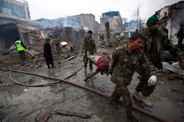 Afghan soldiers carrrying away a victim in the aftermath of one of the devastating attacks by Taliban fighters in the heart of Kabul's commercial district yesterday