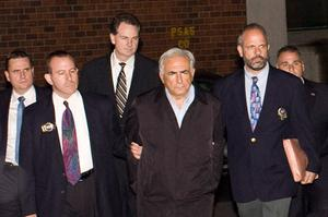 International Monetary Fund chief Dominique Strauss-Kahn, in handcuffs, is walked to a police vehicle outside of a New York City Police Department facility on W. 123rd St. Photo: Getty Images
