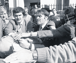 Detectives bundle a hooded Malcolm Macarthur into a patrol car to be dispatched to Mountjoy Jail.
