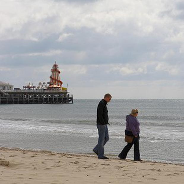 A couple stroll on the beach in Bournemouth which has launched its own weather service