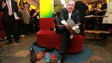 Labour's Pat Rabbitte tries on a pair of shoe's in Korky's shoe shop on Grafton Street Dublin today during the media briefing on Labour's plan to abolish upward-only rent reviews. Photo: PA