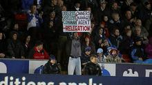 A Blackburn Rovers fan holds up a banner at Ewood Park as the team are relegated. Photo: PA