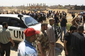 Residents and members of the Free Syrian Army watch as United Nations monitors make a surprise visit to Qusair town near Homs city, northern Syria. Photo: Reuters