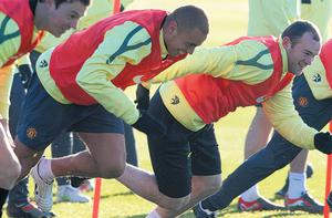 Manchester United players (l-r) Jonny Evans, Wes Brown and Wayne Rooney go through their paces at Carrington yesterday