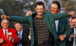 Last year's champion Phil Mickelson helps Masters winner Charl Schwartzel with his green jacket. Photo: AP