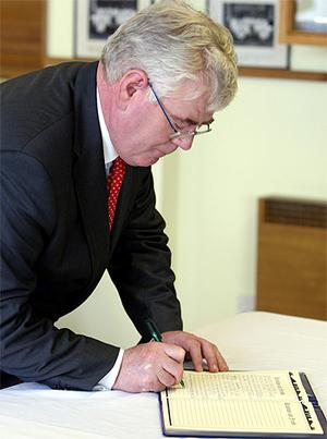 Tanaiste Eamon Gilmore signs a book of condolence at Ravenhill rugby ground, Belfast, in memory of rugby player Nevin Spence