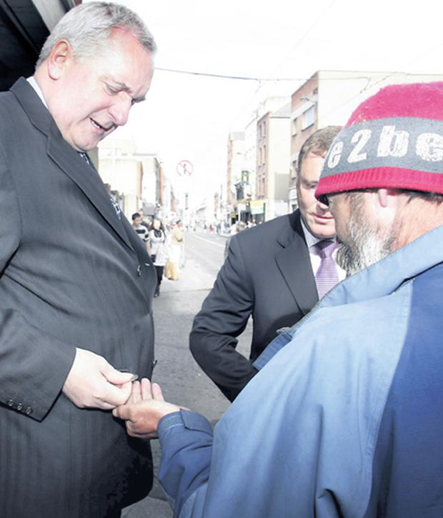 Taoiseach Bertie Ahern gives a homeless man some change after leaving Today FM's Last Word Show yesterday