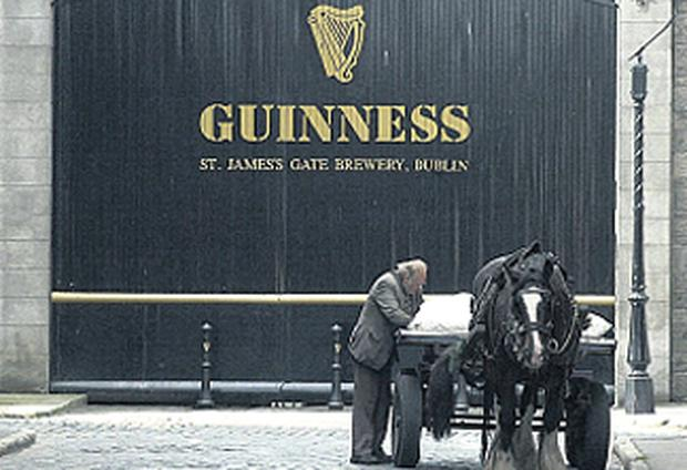 A man and his dray horse stop to adjust their load outside the Guinness gates.