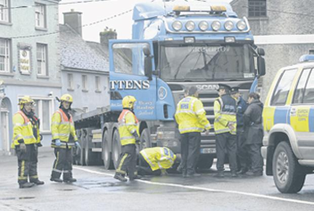 Gardai and emergency service personnel examine a lorry after a 12-year-old boy was struck and killed in Main Street, Mountrath, Co Laois yesterday. The boy was on his way home from a sweet shop when the tragedy happened